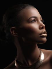 Fototapete - Fashion studio portrait of an extraordinary beautiful nude african american model with perfect smooth glowing mulatto skin, make up, full golden lips, shaved haircut and gold necklace, profile