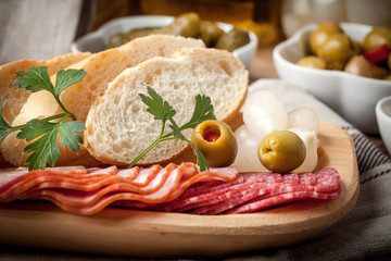 Tapas with sliced sausage, salami, olives, marinated onions, cuc