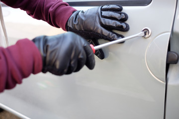 Hands of a thief trying to open a car door lock