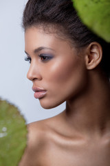 Fototapete - Beauty studio portrait of a beautiful metis model with smooth pure mulatto skin, fresh makeup and full lips, light background