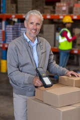 Portrait of warehouse manager scanning the boxes