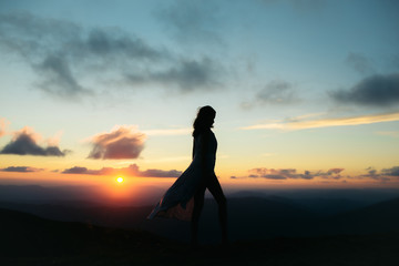 woman at sunset or sunrise in mountains