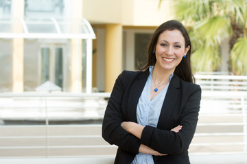 Successful business woman looking confident and smiling, outside