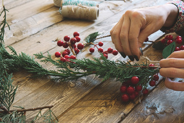 Florist at work: Creating a wooden wreath with christmas  red ba