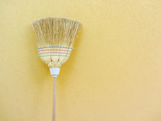 isolated country broom on yellow background