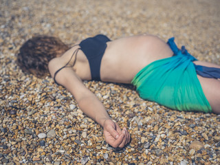 Pregnant woman in sarong lying on the beach