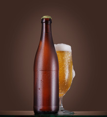 Bottle and glass of beer on the table over beige background