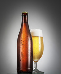 Bottle and glass of beer on the wooden table over grey backgroun