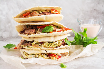 Meat pita bread with yogurt sauce and mint leaves