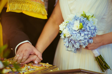 groom and bride  puts his hand on the holy book