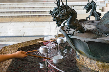 Person filling up ladle with water of chozuya fountain