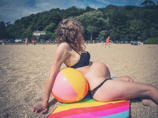pregnant woman sitting with beach ball