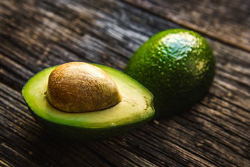 Fresh Avocado sliced over vintage wooden background close up.
