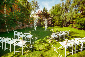 White garden chairs stand in the front of wedding altar