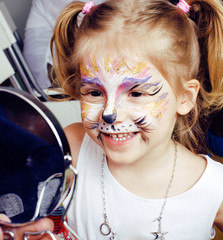 little cute blonde girl with faceart on birthday party having fun happy smiling, lifestyle people concept, halloween preparation