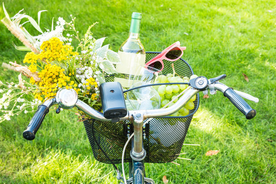 Romantic picnic - flowers and wine in bicycle basket