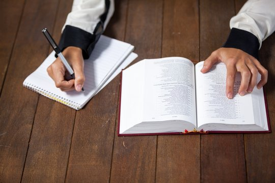 Woman with a bible writing on notepad