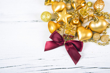 Brilliant gold baubles and cones like christmas decoration. Yellow balls ribbon, gift, red bow and tinsel isolated on white wooden background.