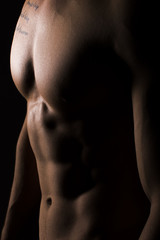 Muscular Torso of Sexy Young Male Close Up on Black Background