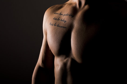 Sexy Muscular Man Tattooed Torso on Black Background. Male Chest Close Up.