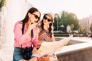 two attractive woman tourists looking at the map in the city