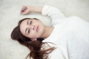 portrait of brunette woman lying on carpet
