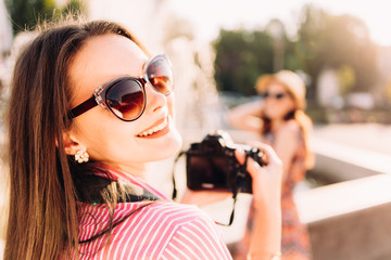 girls taking pictures on film camera outdoor in the city