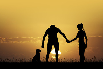 couple with dog at sunset