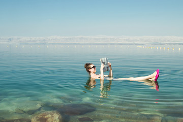 Girl reading newspaper floating on surface Dead Sea enjoy summer sun and vacation. Recreation tourism, healthy lifestyle, free time concept