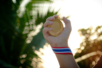 hand raised and holding gold medal against sky. award concept