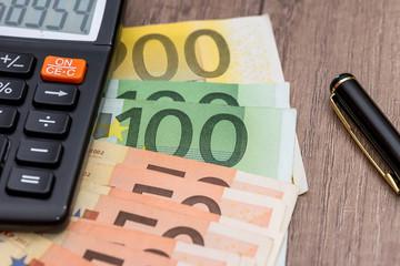 euro, calculator and pen on desk