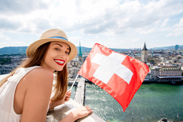 Young female tourist with swiss flag on the top of the tower in Zurich city. Woman having a great vacation in Switzerland