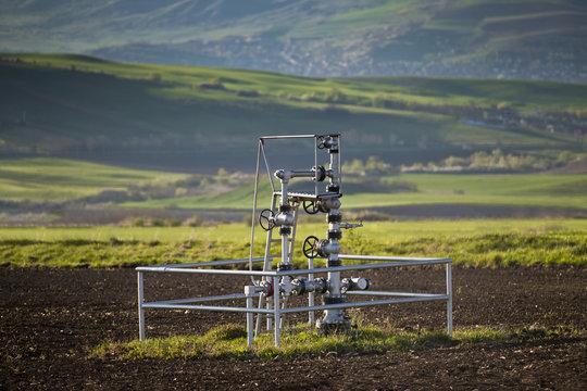 Natural gas wellhead in a meadow of green grassland field