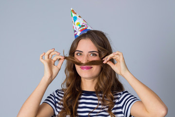 Woman in celebration cap making moustache of her hair