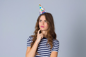 Woman in celebration cap thinking