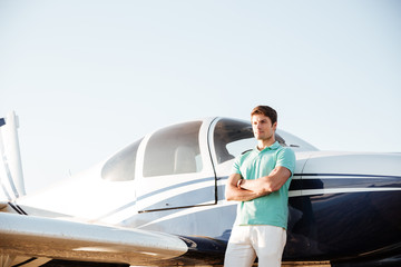 Confident young man standing in front of small airplane