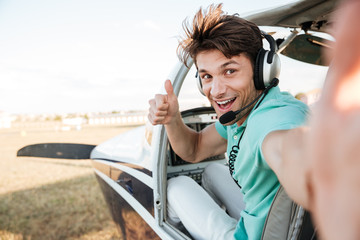 Cheerful pilot sitting in airplane cabin and showing thumbs up