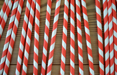 Red and White striped party straws on a wood background texture