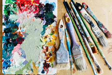 Brushes with palette in the creative background. Colorful element.