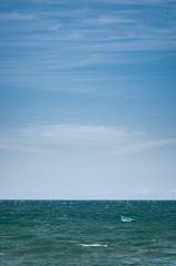 An empty blue boat floating on the ocean.