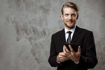 Young successful businessman smiling, holding tablet over grey background.