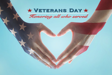 Veterans day holiday celebration concept: American flag pattern on human hands in heart sign shape, text message honor all who served for brave military on blue background