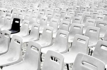 Fila di sedie vuote bianche, una sola nera