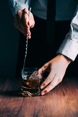 Man Preparing a Glass of whiskey on a wooden table