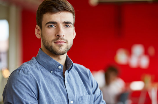 Confident male designer working in red creative office space
