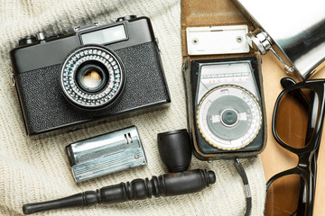 Accessories of the creative person. 35-mm film camera, exposure meter in leather case, steel flask, sunglasses and smoking set on wooden background.