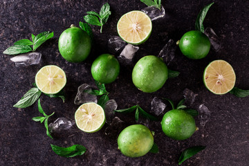 Lime background. Fresh limes with slices and mint leaves around.