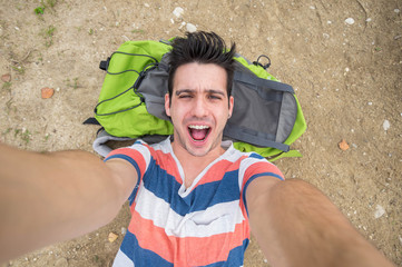 Handsome traveller taking a selfie lying on the ground