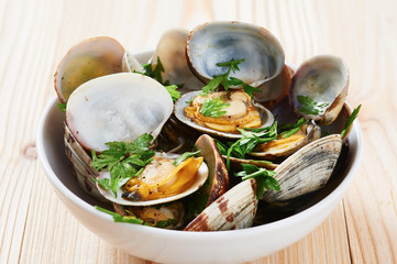 Steamed clams in white bowl on wooden table