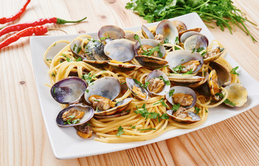 Pasta with steamed clams in white square dish